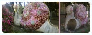 Скульптура обтекаемой формы из светлого материала с отделкой разноцветными кусочками плитки